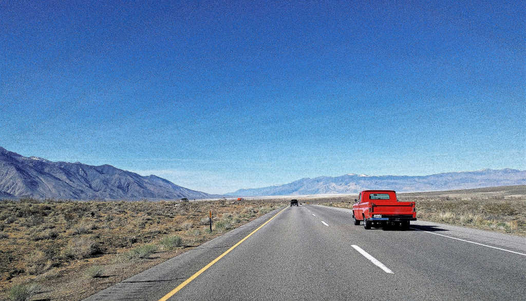 Driving US 395 North to Bishop, California. Red truck in right lane